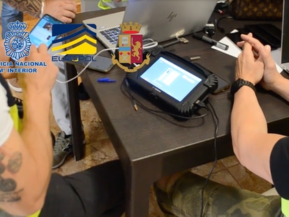Agentes de la Policía emplean un dispositivo habitual para copiar la información de uno de los móviles de los detenidos. La imagen procede de un vídeo de la Policía sobre la operación en Tenerife.