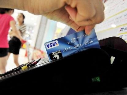 Un hombre paga con una tarjeta, en China.
