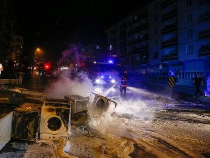 Un bombero extingue algunos de los productos quemados por manifestantes turcos durante su asalto a negocios y viviendas de refugiados sirios en el distrito de Altindag, en Ankara.