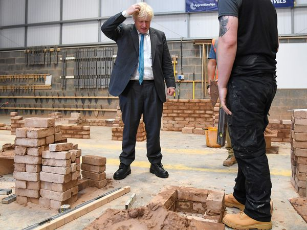 TOPSHOT - Britain's Prime Minister Boris Johnson reacts as lays bricks whilst talking with students during his visit to Exeter College in Exeter, southwest England on September 29, 2020. (Photo by Finnbarr Webster / POOL / AFP)