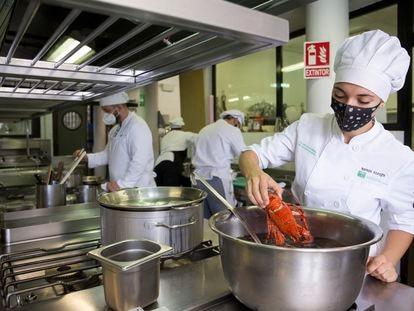 Varios alumnos de la escuela de hostelería La Cónsula, en Málaga, preparan el menú del día.