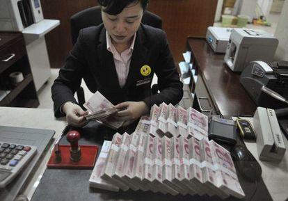 Una mujer cuenta billetes de 100 yuanes, en Hefei, China.