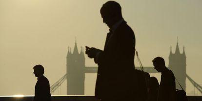 Unos directivos manejan sus móviles en Londres.