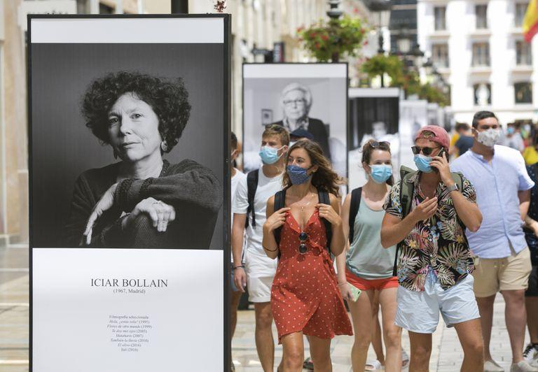 Paseantes, ayer al mediodía, por la calle Larios, en Málaga, donde se ha instalado una exposición de fotografías dedicada al festival.