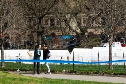 Dos jóvenes se hacen una foto cerca del hospital de campaña levantado en Central Park, en Nueva York. EDUARDO MUÑOZ