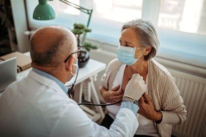 Un doctor examina el corazón de una paciente.