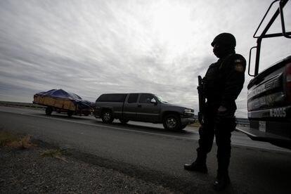 Un policía estatal de Nuevo León custodia la carretera ante la llegada de visitantes.