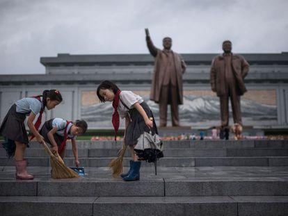 Tres estudiantes limpian los escalones que sitúan frente a las estatuas de los líderes norcoreanos Kim Il-Sung y Kim Jong-Il con motivo de la celebración del 'Día de la victoria' en Pyongyang (Corea del Norte).