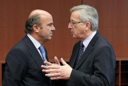 El ministro de Economía, Luis de Guindos, escucha al presidente del Eurogrupo, Jean-Claude Juncker