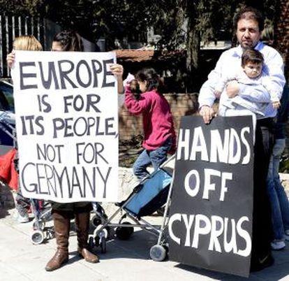"""Un hombre sostiene una pancarta en la que se puede leer """"mantened vuestras manos lejos de Chipre"""". A su lado, una mujer que sostiene otra en la que se puede leer """"Europa es para su gente no para Alemania"""" frente al Parlamento en Nicosia (Chipre)."""