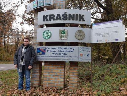 """Cezary Nieradko, del colectivo LGTB, frente a un cartel del municipio de Krasnik, una de las ciudades polacas autodenominadas """"libres de ideología LGTB"""" el pasado 31 de octubre."""