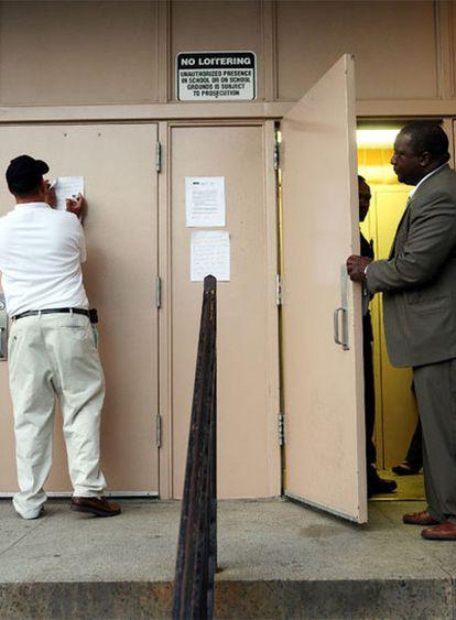 Un empleado de un colegio coloca un cartel por el cierre como medida preventiva ante la propagación de la gripe A.