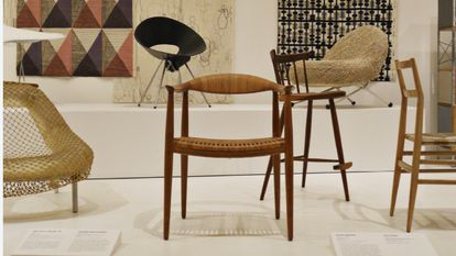 In the center, a copy of The Round Chair by Hans J. Wegner in the permanent exhibition of MoMA (Museum Of Modern Art, New York).  The museum received this specimen in 1953 as a gift from Georg Jensen.  I PP Møbler.