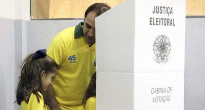 Un hombre vota acompañado de su hija en Belo Horizonte