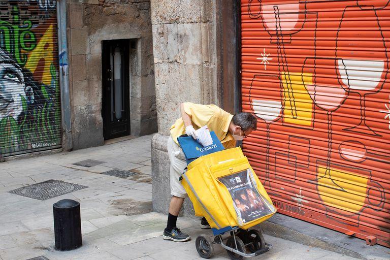 Un cartero deja correo en un local del barri Gòtic de Barcelona.