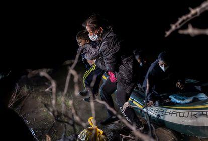Una madre migrante cruza con su hijo en brazos el Río Bravo a la altura de Roma, Texas, el pasado 30 de abril.