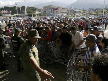 Guardias nacionales controlan la entrada de un supermercado privado en San Cristóbal. / e. ramírez (REUTERS)