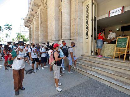 Ciudadanos hacen fila para comprar en una cafetería este sábado, en La Habana (Cuba).
