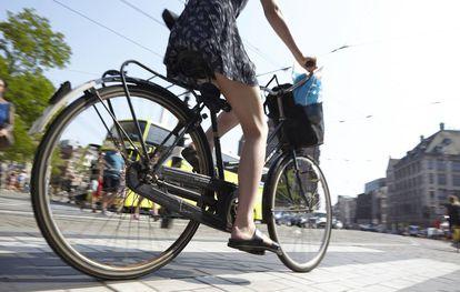 Mujer pedaleando en Ámsterdam, en Países Bajos.