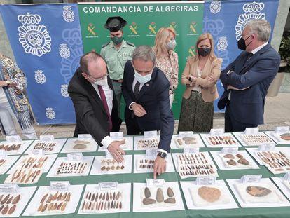 El catedrático de Prehistoria, José Ramos, muestra el subdelegado del Gobierno en Cádiz, José Pacheco, parte de los mil útiles prehistóricos recuperados en una operación de la Guardia Civil y la policía en Algeciras.