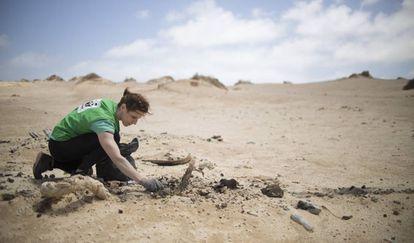 Una voluntaria recoge plásticos llegados a través del mar.
