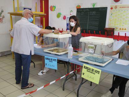 Un elector deposita su voto en un colegio de Marsella.