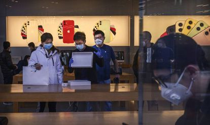 Dependientes atienden en una tienda de Apple en Pekín.