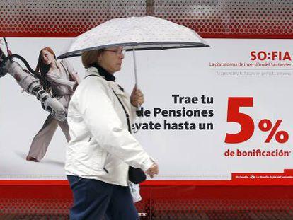 Una mujer camina frente a una sucursal bancaria en la que se anuncian planes de pensiones.
