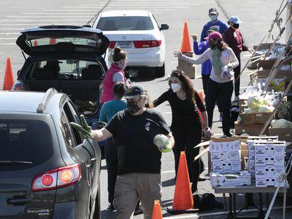 Voluntarios entregan alimentos a vehículos en un centro de distribución en Connecticut, EE. UU. (Foto AP / Mark Lennihan)
