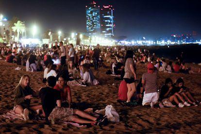 Varias personas celebran en la playa de la Barceloneta la noche de San Juan el 24 de junio.