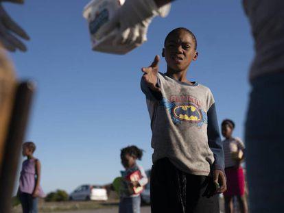 Un niño residente en el asentamiento informal de  Masincedane, en Ciudad del Cabo (Sudáfrica) recibe una ración de comida de parte de una organización benéfica el pasado 28 de abril de 2020.