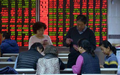 Inversores juegan a las cartas en una empresa de valores en Pekín.
