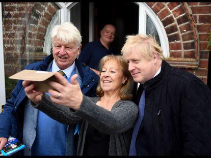 Boris Johnson junto a su padre, Stanley, se hacen una foto con una votante conservadora en 2019.