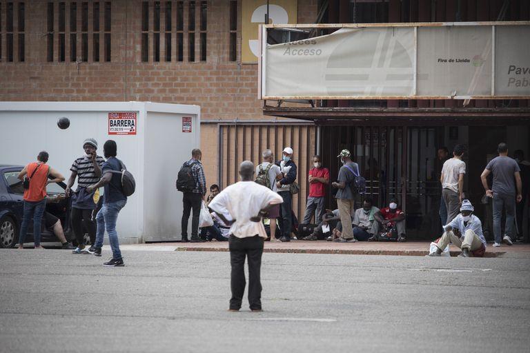 Un grupo de temporeros esperan entrar en el recinto ferial de Lleida.