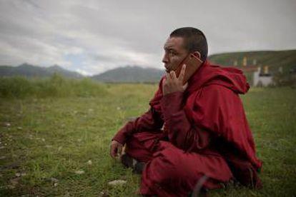 Un tibetano budista habla por teléfono, en Yushu County