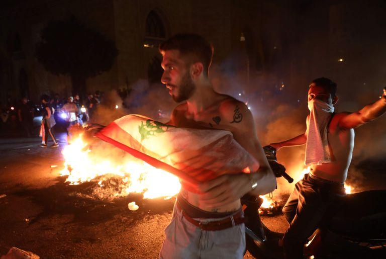 Unos manifestantes, la noche de este jueves durante los disturbios en Beirut.