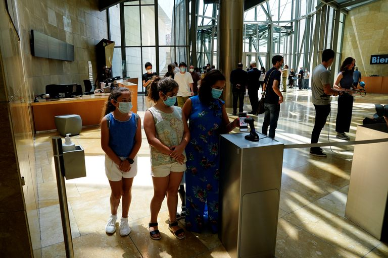 Visitantes usando su móvil a la entrada del museo Guggenheim en Bilbao el 3 de junio.