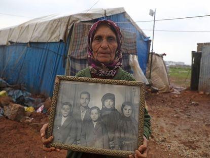 Una desplazada siria muestra una foto familiar en una aldea de Idlib.