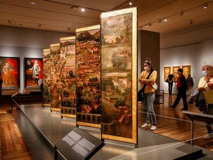 Varios visitantes observan 'Obrador de los Correa', un biombo que forma parte de la exposición 'Tornaviaje: Arte iberoamericano en España', en el Museo del Prado.