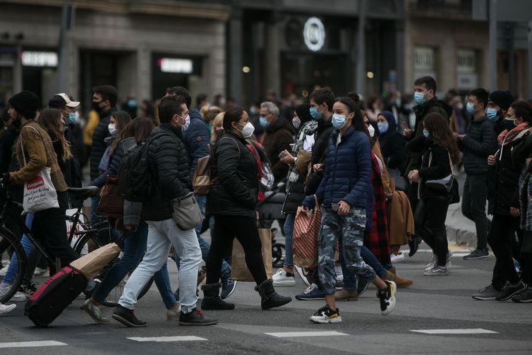 Decenas de personas cruzan el paso de peatones que comunica plaza Catalunya con la Rambla en Barcelona