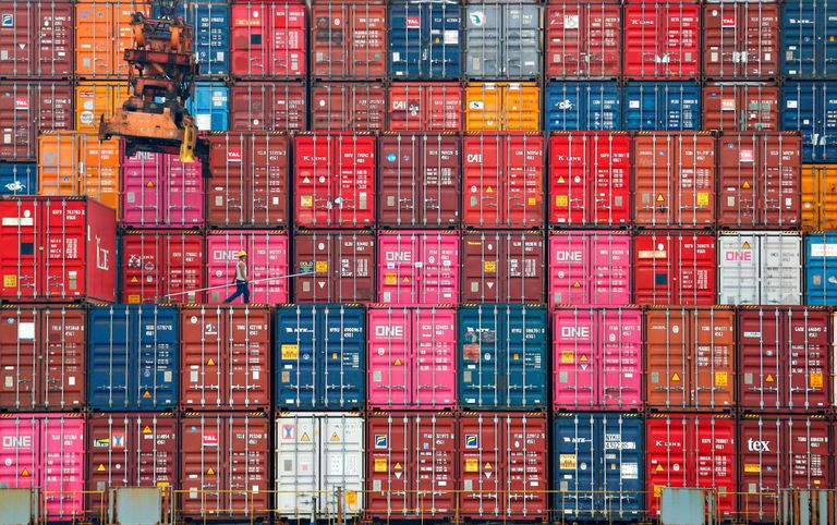 A worker walks on stacks of containers at the port of Tanjung Priok in Jakarta, Indonesia.