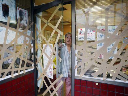 El dueño de una cafetería prepara los cristales de su establecimiento ante la llegada del tifón, en Uwajima, al suroeste de Japón.