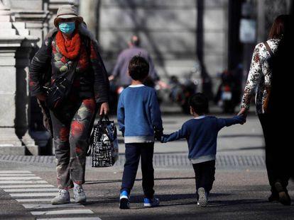 Un par de niños cruzan de la mano de su madre una calle en Madrid.