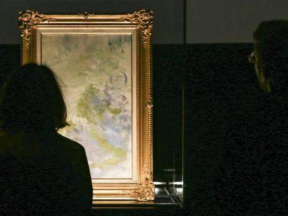 Dos personas observan el cuadro nunca visto de Claude Monet, en el centro Ideal.