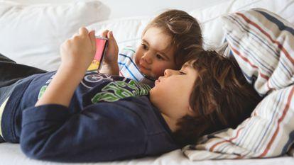 Uno niños miran dibujos animados en un dispositivo móvil en casa.