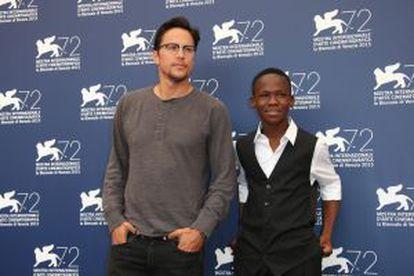Cary Fukunaga y el actor Abraham Attah, director e intérprete de 'Beasts of No Nation', posan esta mañana ante los fotógrafos en Venecia.