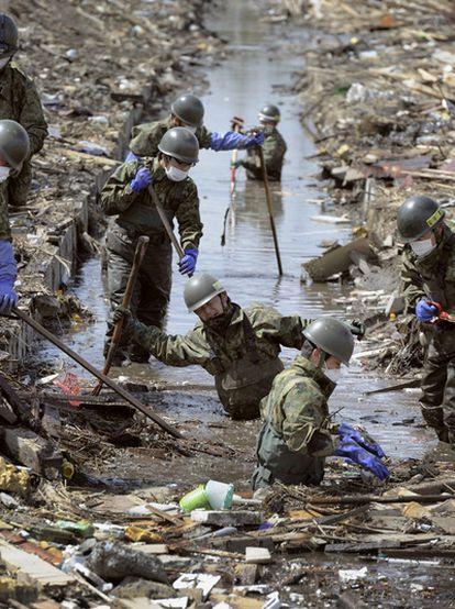 Soldados japoneses buscan  cadáveres de las víctimas del terremoto y del tsunami en Shichigahama, al noreste del país.