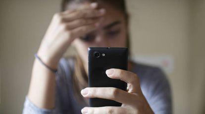 Una joven consulta su móvil.