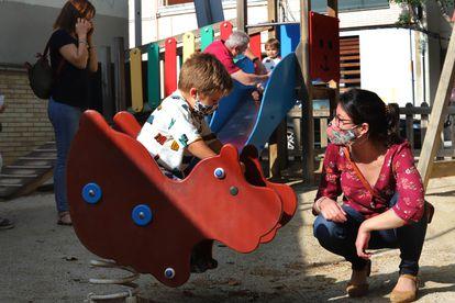 Varios padres, con sus hijos, en un parque infantil en Terrassa.