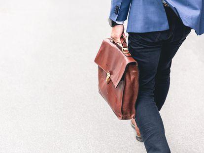Un profesional camina con su maletín de trabajo.
